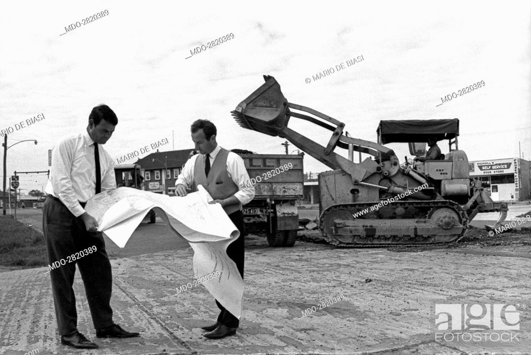 Stock Photo: Italian brothers Lorenzo Galli and Michele Galli, owners of a company in Melbourne skilled in street building, watching a plan in the middle of a building site.