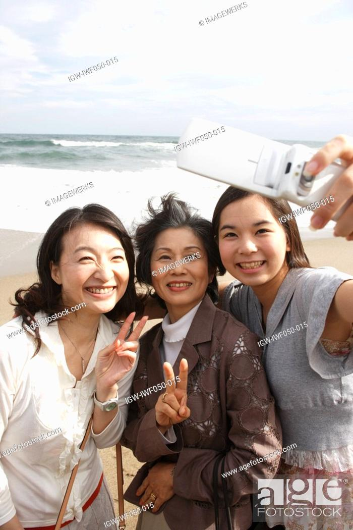 Stock Photo: Daughter 14-15 with mother and grandmother photographing self.