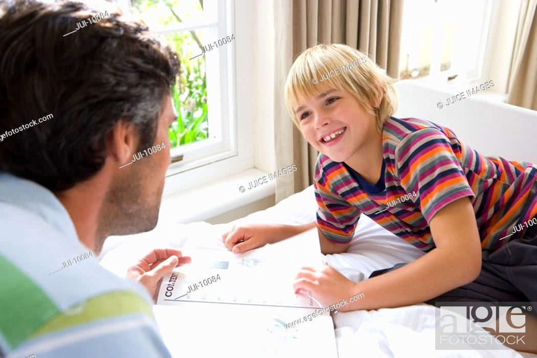 Stock Photo: Boy 6-8 looking at book with father, smiling.