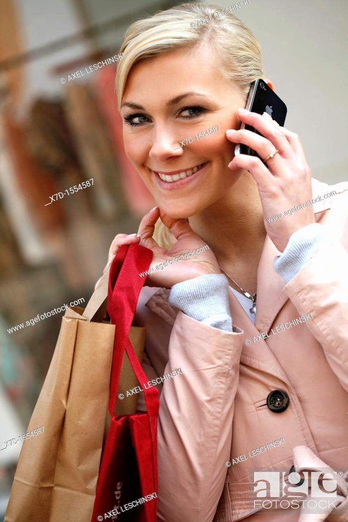 Stock Photo: portrait of woman take a call on a cell phone in the city.