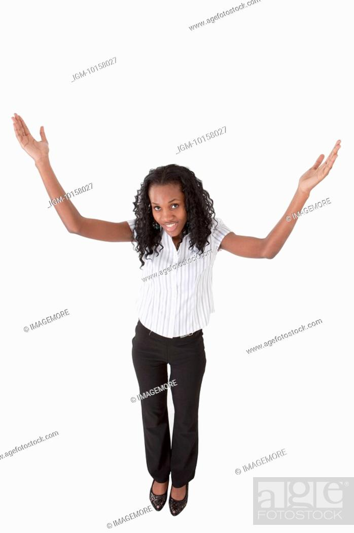 Stock Photo: Young woman standing and looking up with hands outstretched.