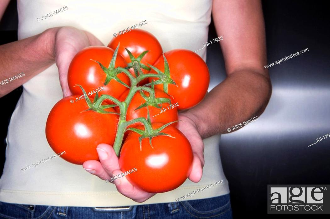 Stock Photo: Close up of woman holding fresh tomatoes.