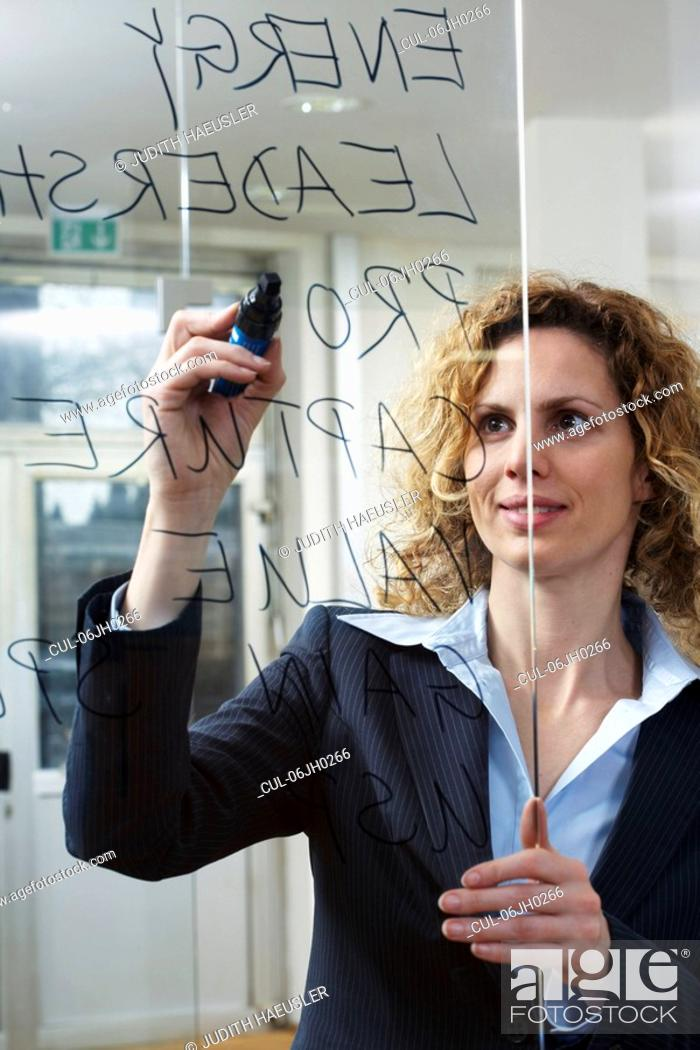 Stock Photo: Businesswoman writing keywords on glass.