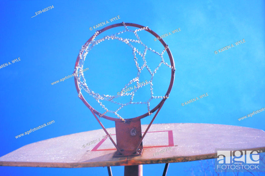 Stock Photo: Basketball hoop seen from below, against almost-cloudless blue sky.
