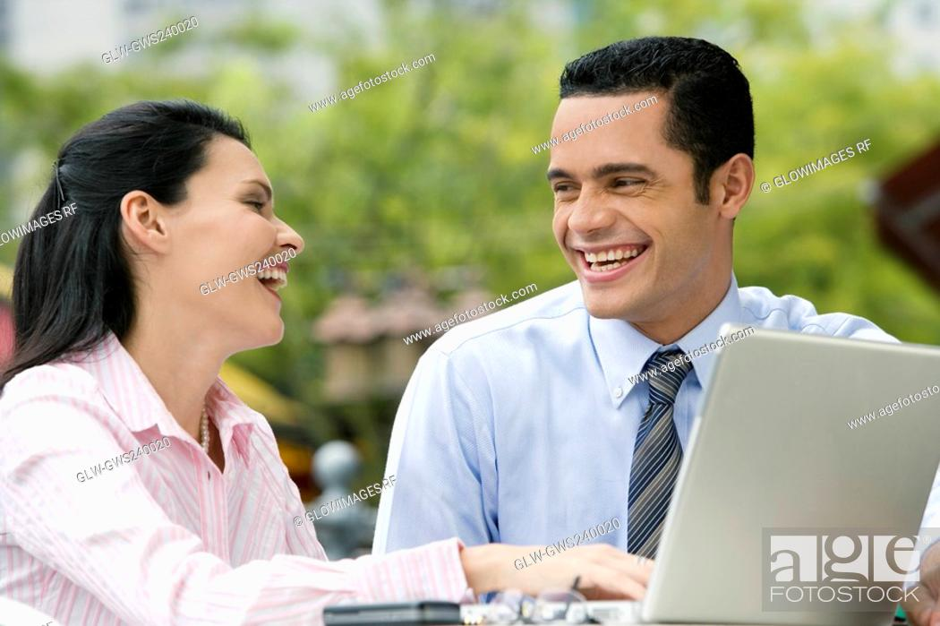 Stock Photo: Close-up of a businessman and a businesswoman looking at each other and smiling.