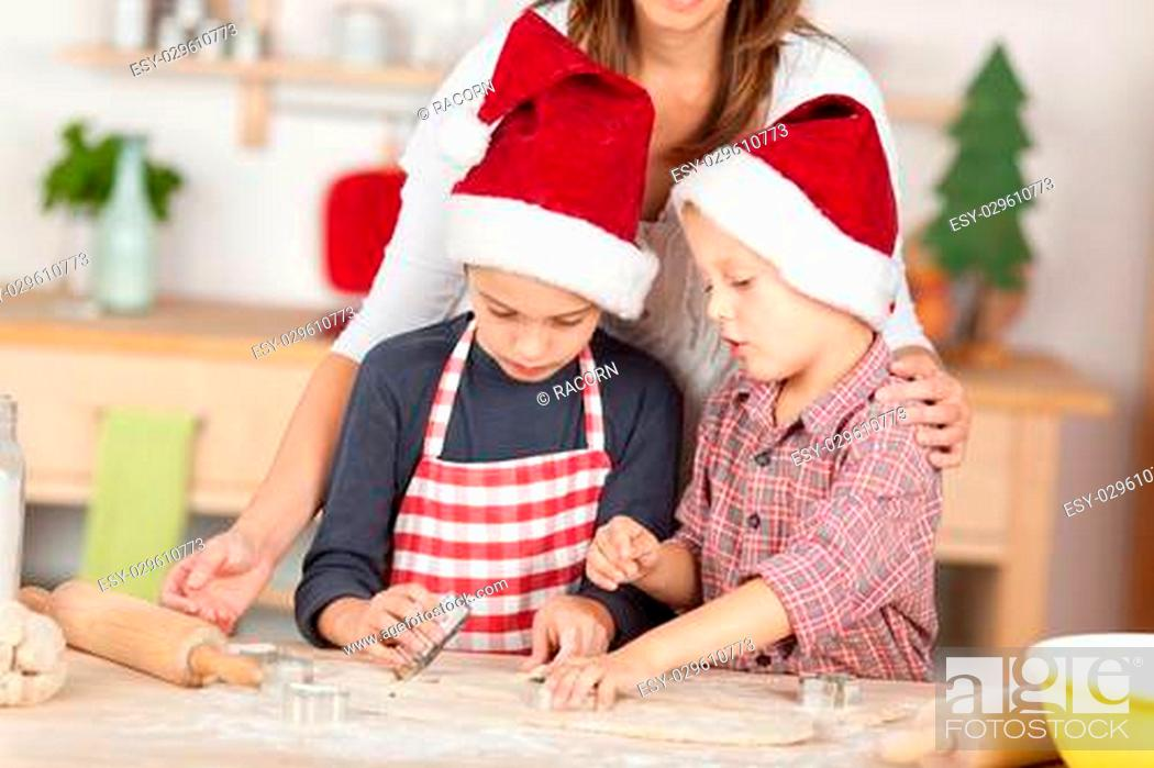 Stock Photo: Two little boys doing gingerbread cookies for Christmas.