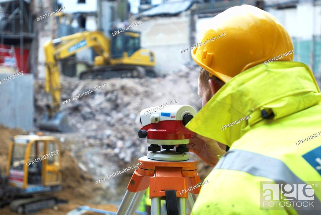 Stock Photo: Surveyor using a theodolite on a construction site.