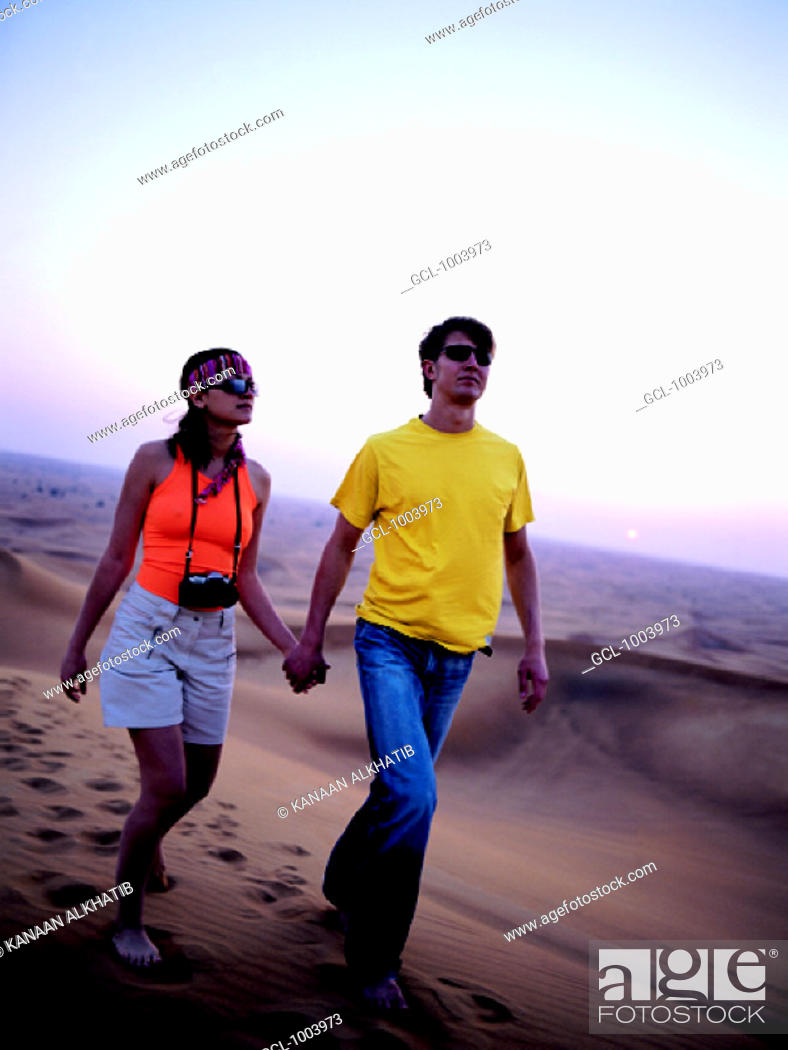 Stock Photo: Young western couple walking through the desert in the United Arab Emirates.