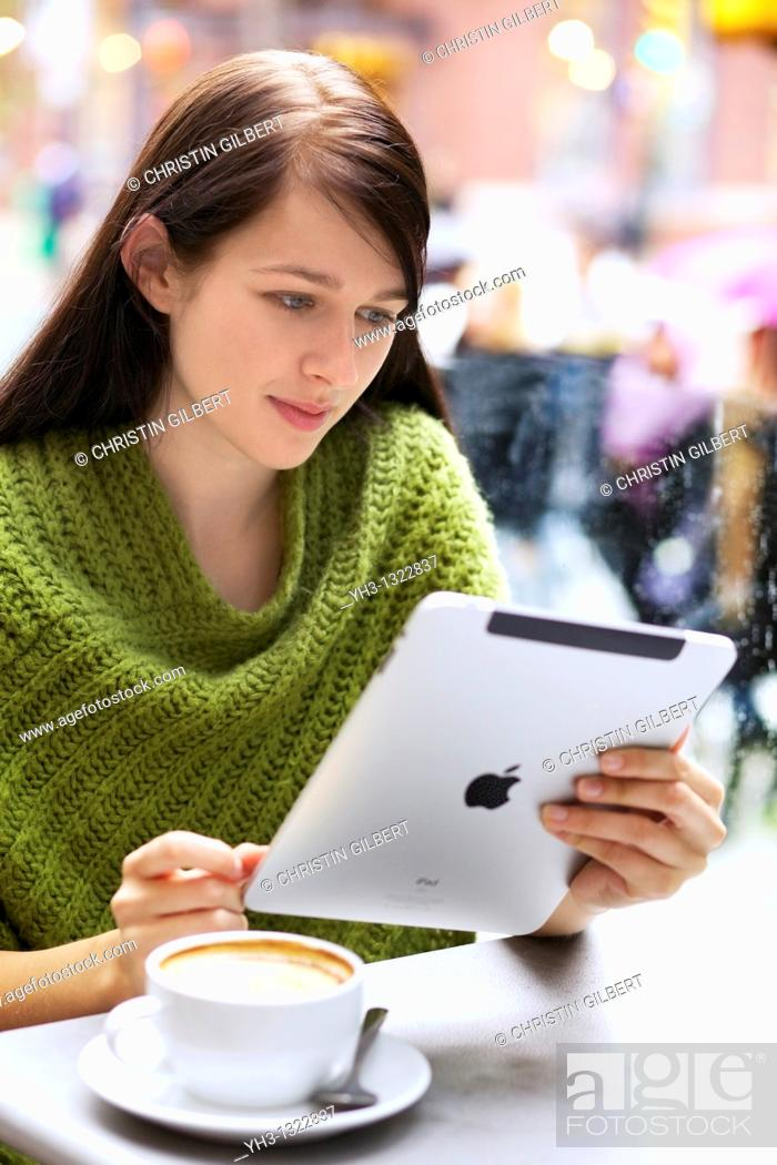 Stock Photo: Young woman relaxing with her Cappuccino while browsing with her iPad outdoor.