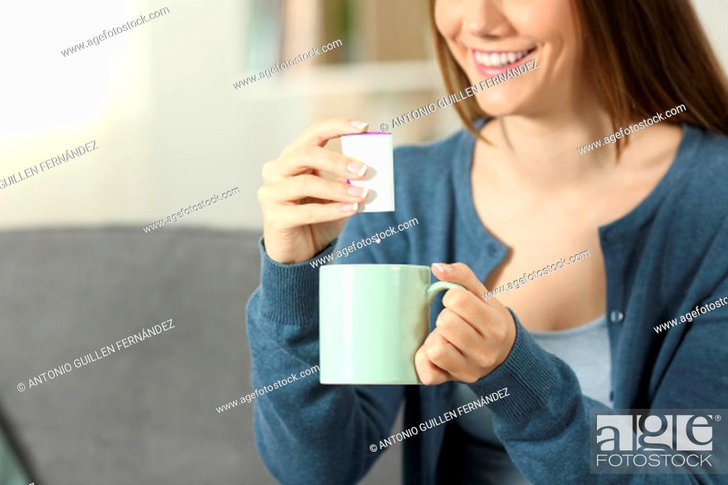 Stock Photo: Close up of a woman hands throwing sacharine pill into a mug sitting on a couch in the living room at home.