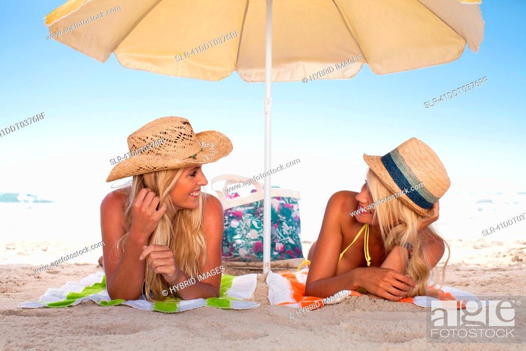 Stock Photo: Women relaxing under umbrella on beach.