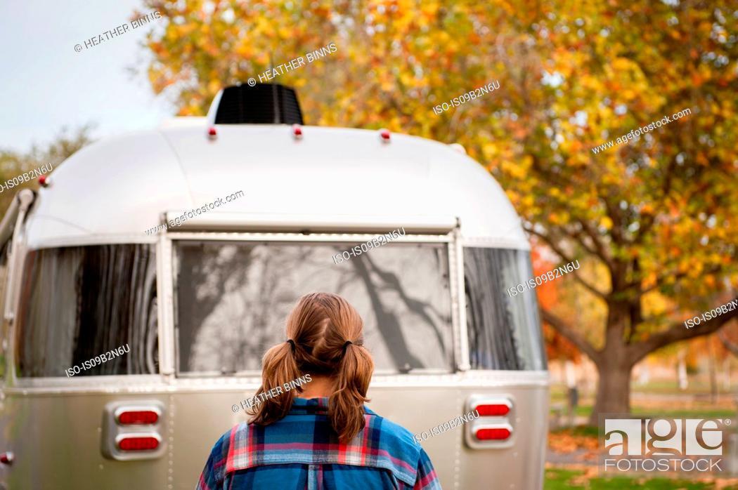 Stock Photo: Rear view of woman looking at camper van, Washington, USA.