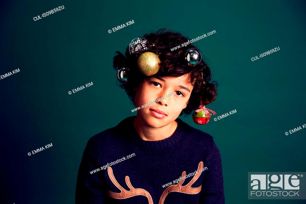 Stock Photo: Portrait of teenage boy wearing Christmas jumper, and baubles in hair.