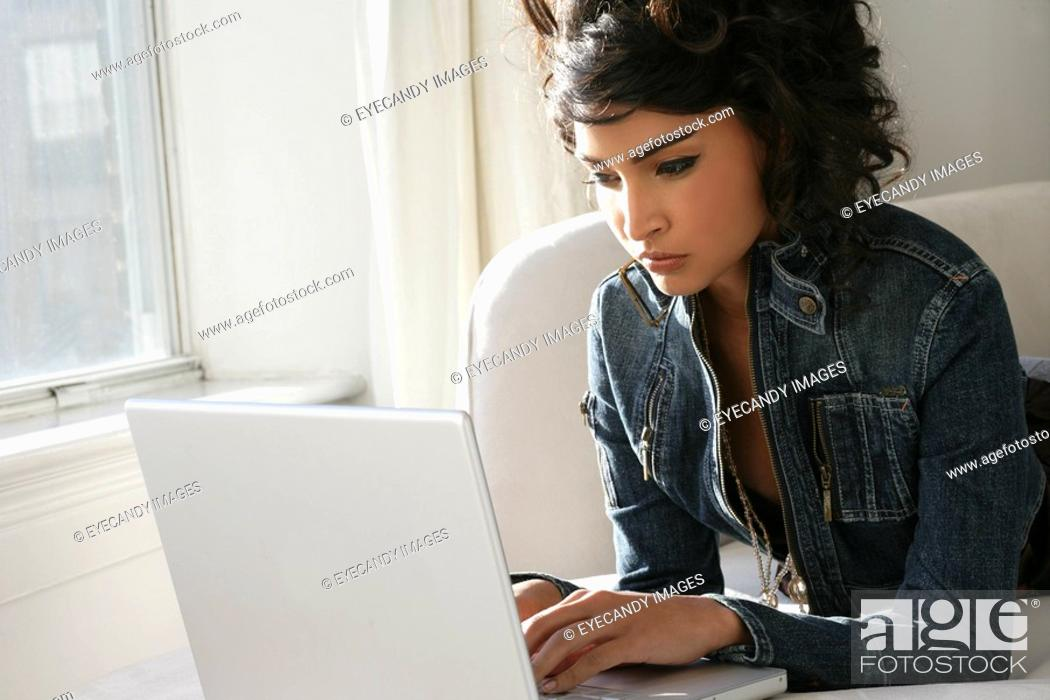 Stock Photo: Young woman using laptop.