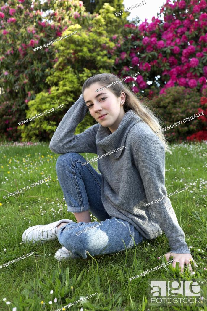 Photo de stock: 16 year old teenager sitting in a park with grass and flowers, taken in Limoges, France.
