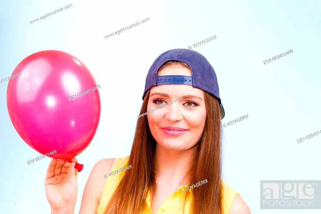 Stock Photo: Joy and fun. Beauty smiling teenage girl with red pink balloon. Young charming trendy woman in fashion clothes against blue background.