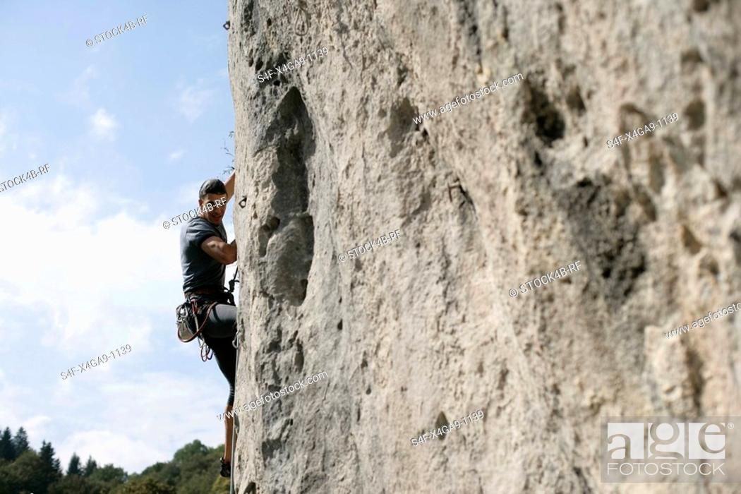 Stock Photo: Young man with black hair climbing up a rocky wall, selective focus.