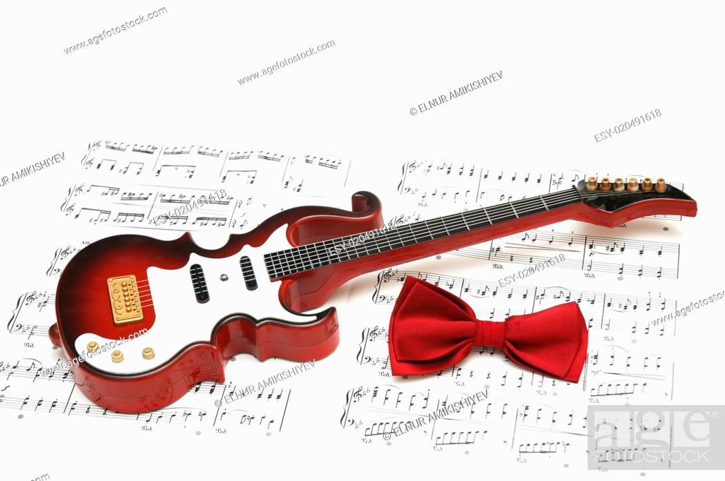 Stock Photo: Musical notes, guitar and bow tie on white.