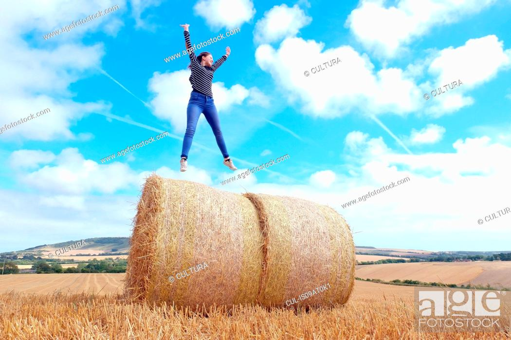 Stock Photo: Young woman jumping on top of haystacks in harvested field.