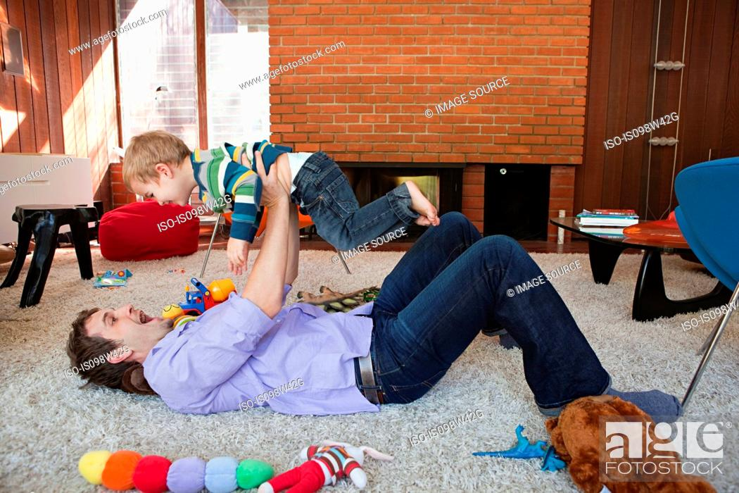 Stock Photo: Father lifting son in living room.