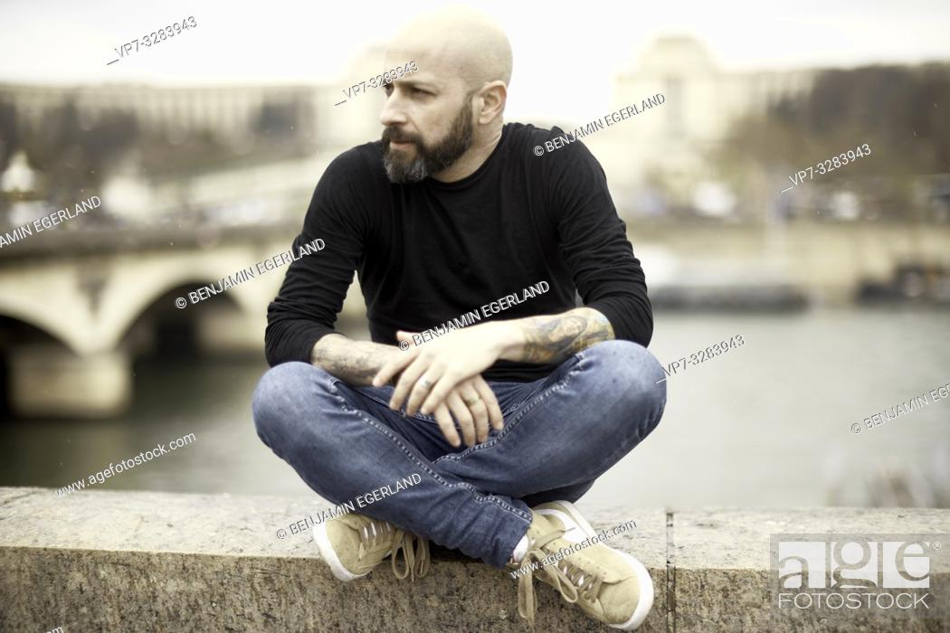 Photo de stock: man sitting at riverbank, Seine river, in Paris, France.