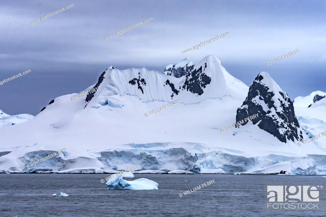 Imagen: Snow Mountains Blue Iceberg Glaciers Charlotte Bay Antarctic Peninsula Antarctica. Glacier ice blue because air squeezed out of snow.