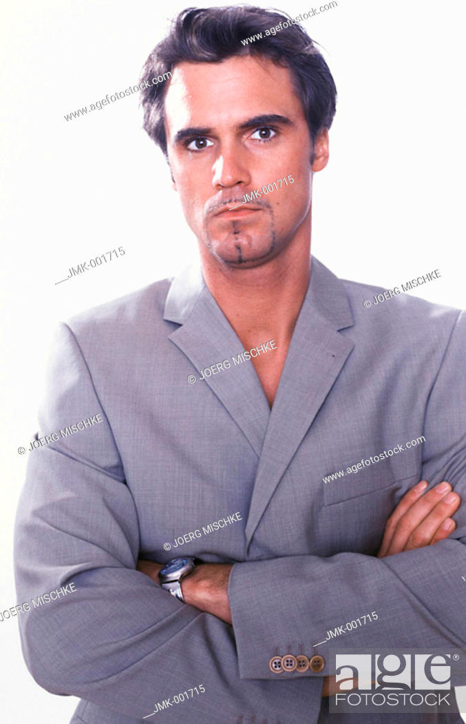 Stock Photo: Portrait of a young man, 20-25 25-30 30-35 dark-haired, masculine, powerful, strong, athletic and beautiful in a grey suit.