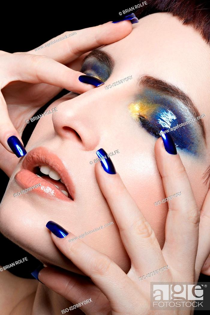 Stock Photo: Young woman with blue nail varnish and eyeshadow touching face.
