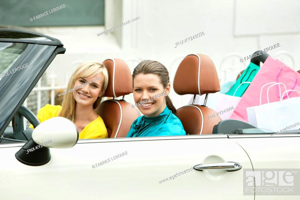 Stock Photo: Two women smiling in a car after shopping.