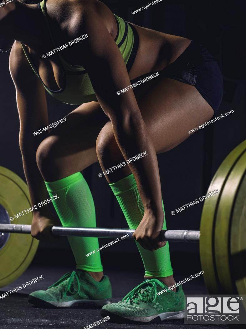 Stock Photo: Young woman preparing to lift barbell.