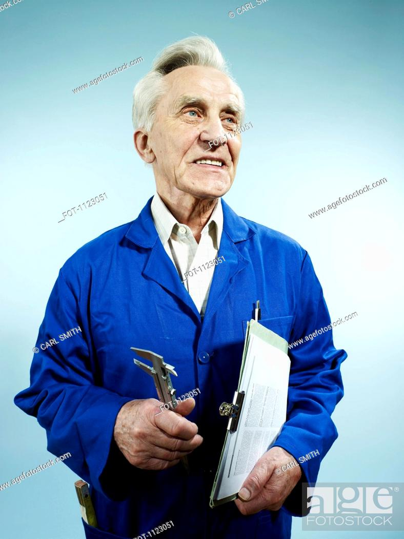 Stock Photo: A cheerful senior man in coveralls carrying a clipboard and work tool.