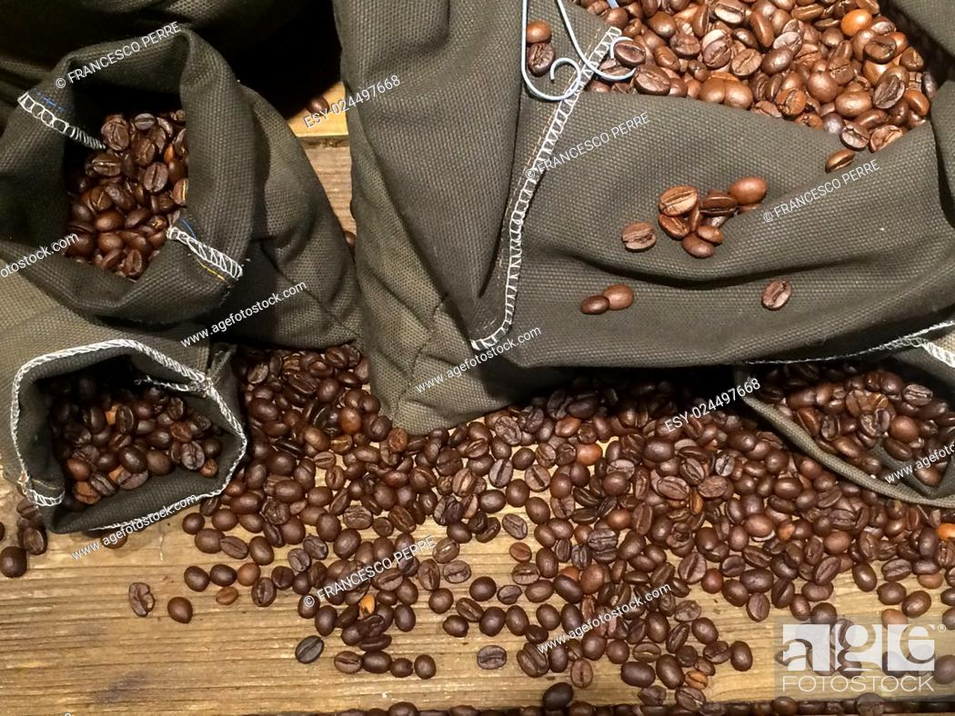 Stock Photo: coffee beans on bags over rustic wood background.