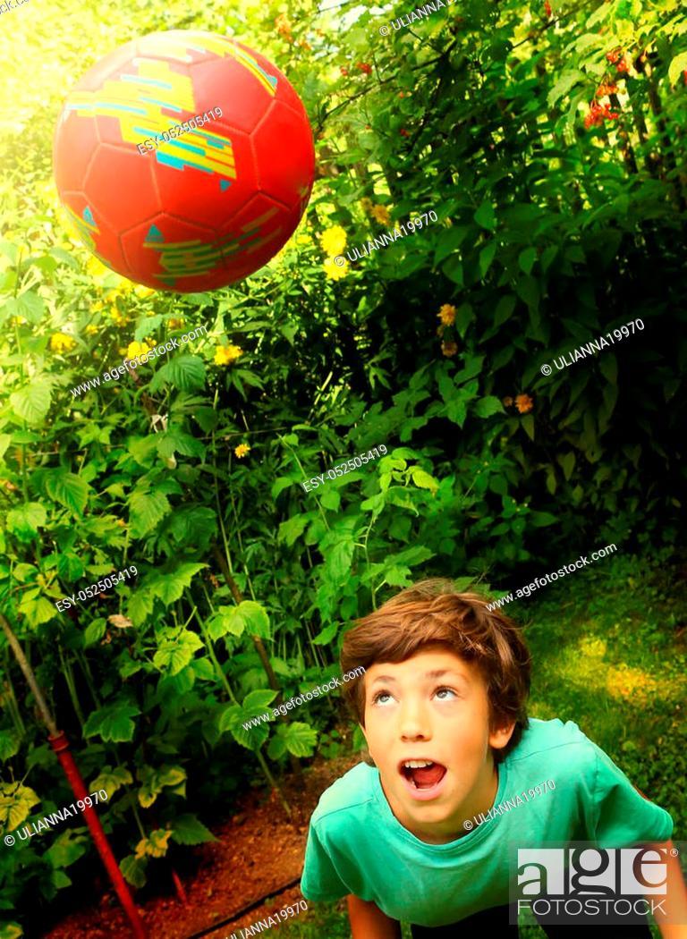 Stock Photo: teen boy play with soccer ball head in the summer garden.