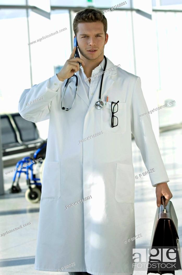 Stock Photo: Male doctor holding a bag and talking on a mobile phone.
