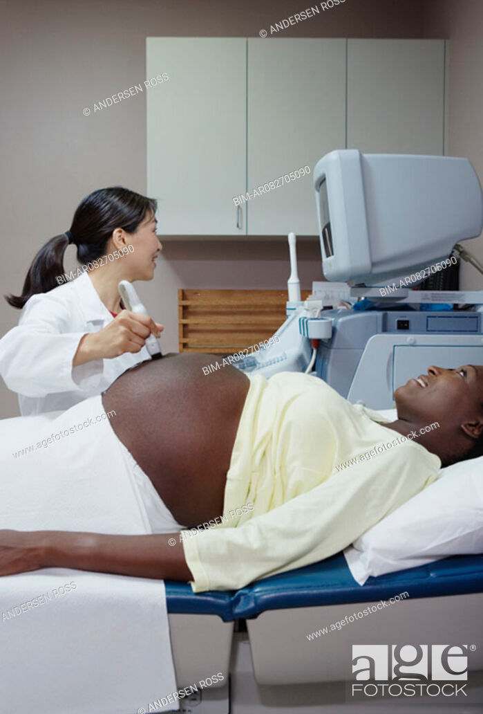 Stock Photo: Technician performing ultra sound on pregnant woman.