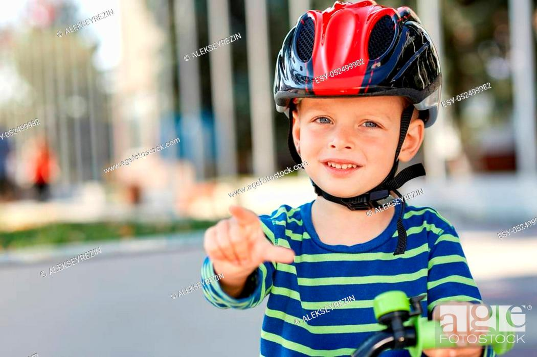 Stock Photo: Kid with bike and helmet smiles while having fun.