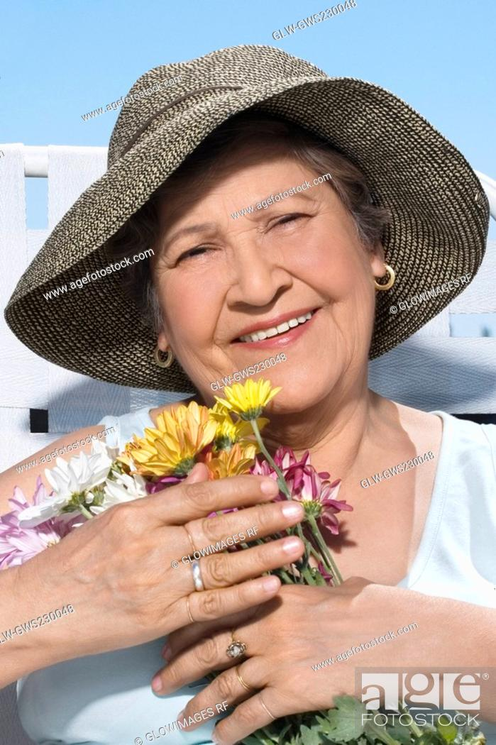 Stock Photo: Close-up of a senior woman holding a bunch of flowers and smiling.