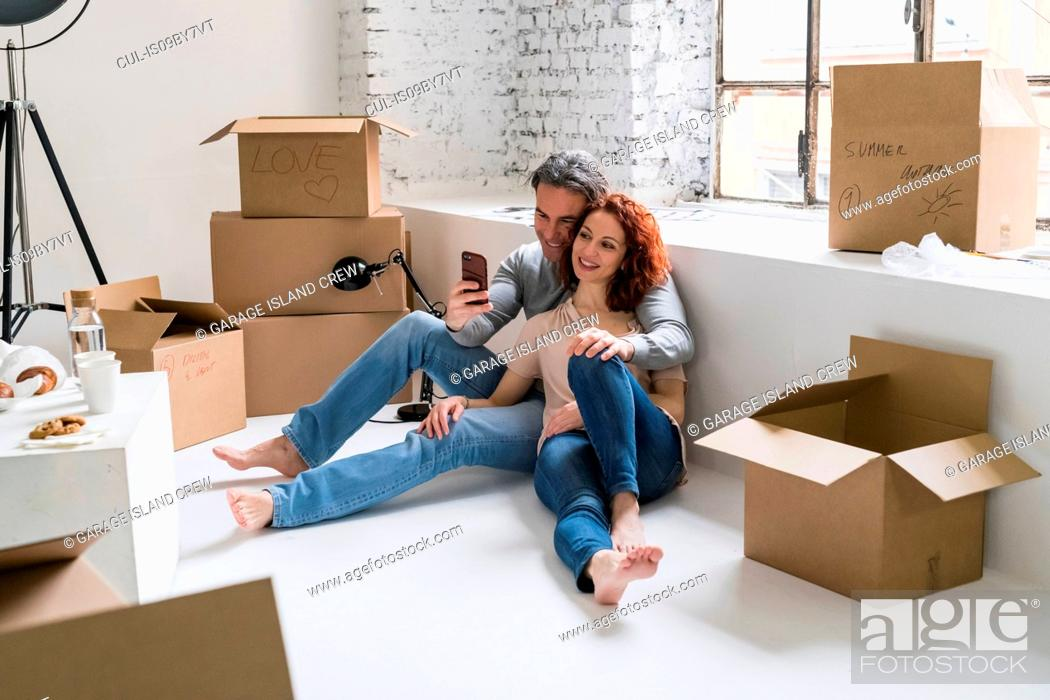 Stock Photo: Couple moving into industrial style apartment, sitting on floor looking at smartphone.
