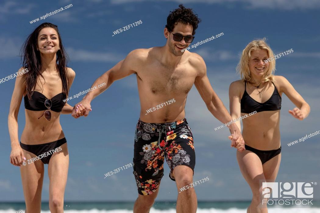 Stock Photo: Happy friends running on the beach.