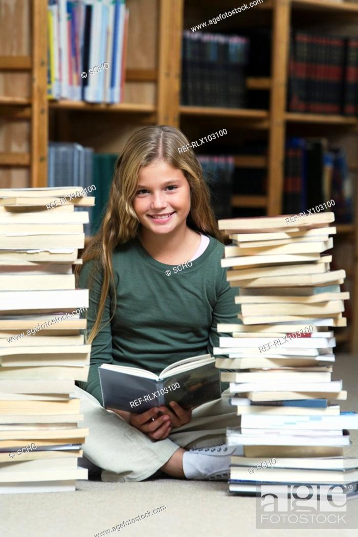 Stock Photo: Girl 10-13 in library, reading and sitting between two piles of school books.