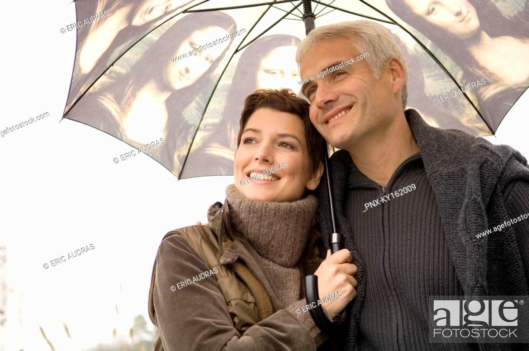 Stock Photo: Close-up of a mid adult woman and a mature man under an umbrella.