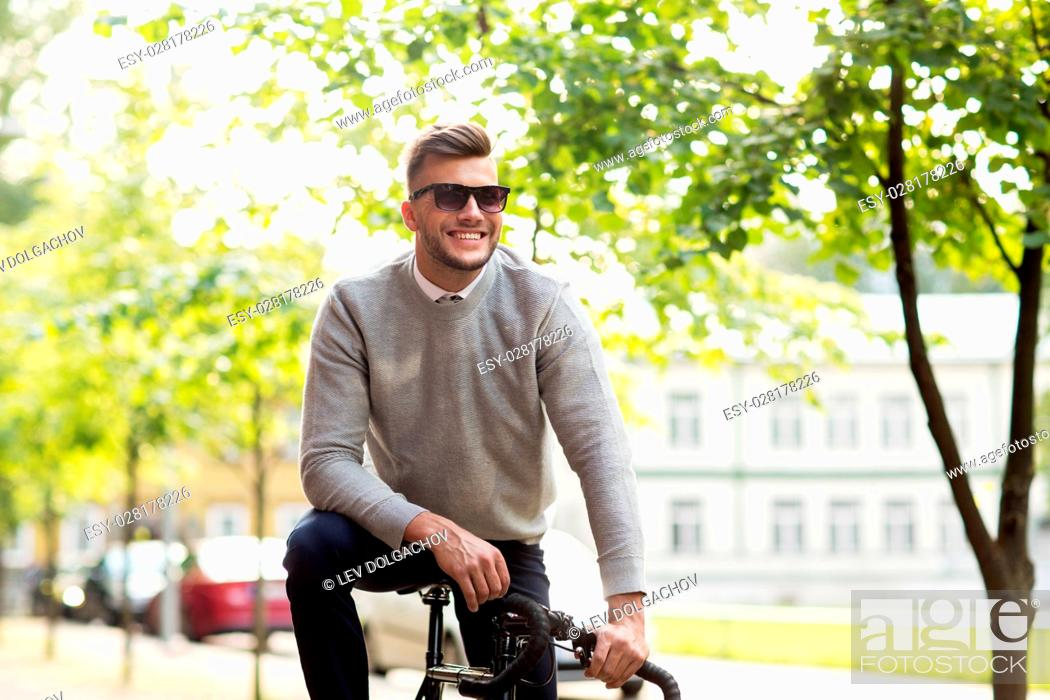 Stock Photo: lifestyle, transport and people concept - happy smiling young man in sunglasses riding bicycle on city street.