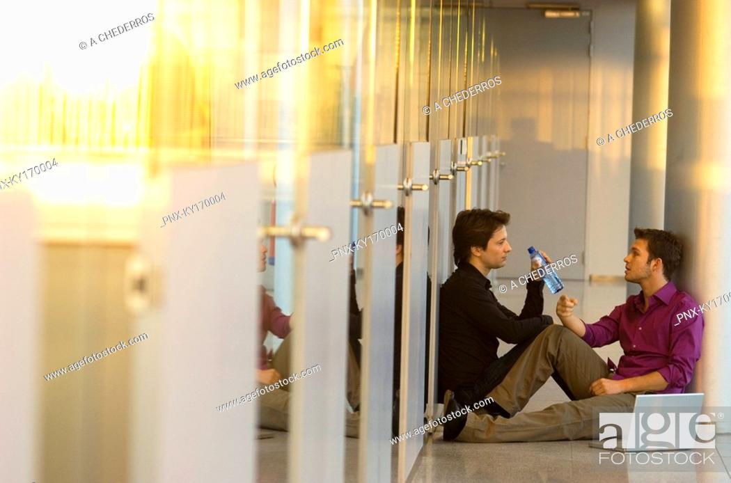 Stock Photo: Two businessmen sitting in a corridor and talking with each other.