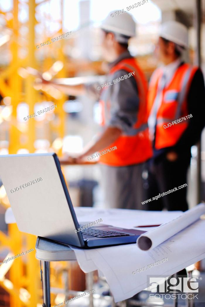 Stock Photo: Construction workers behind laptop and blueprints on construction site.