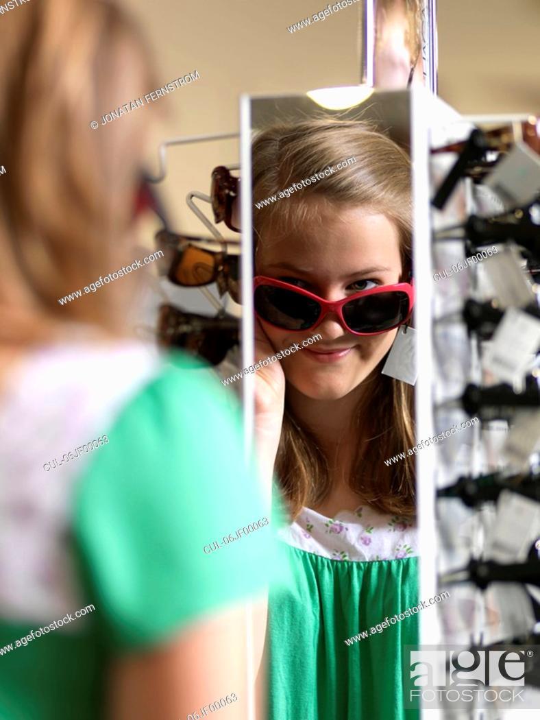 Stock Photo: Girl trying sun glasses.