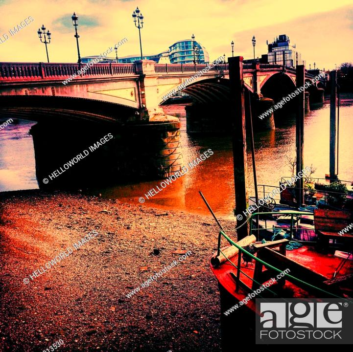 Stock Photo: Houseboats at low tide by Battersea Bridge, London, England.
