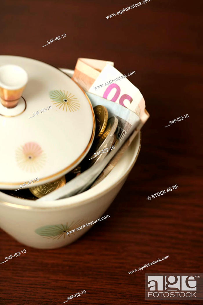 Stock Photo: Sugar bowl filled with Euro bills (part of), close-up.