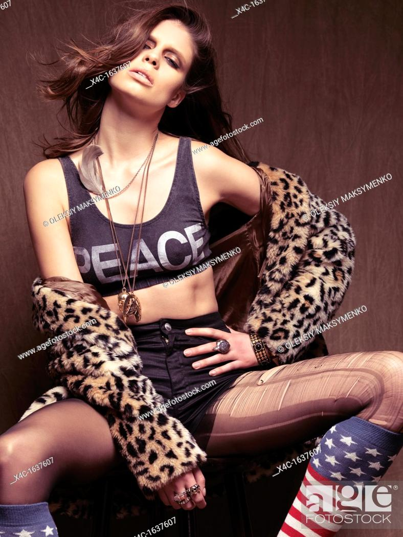 Stock Photo: Fashion photo of a young woman wearing grunge style outfit  Fur coat, ripped tights and American socks.