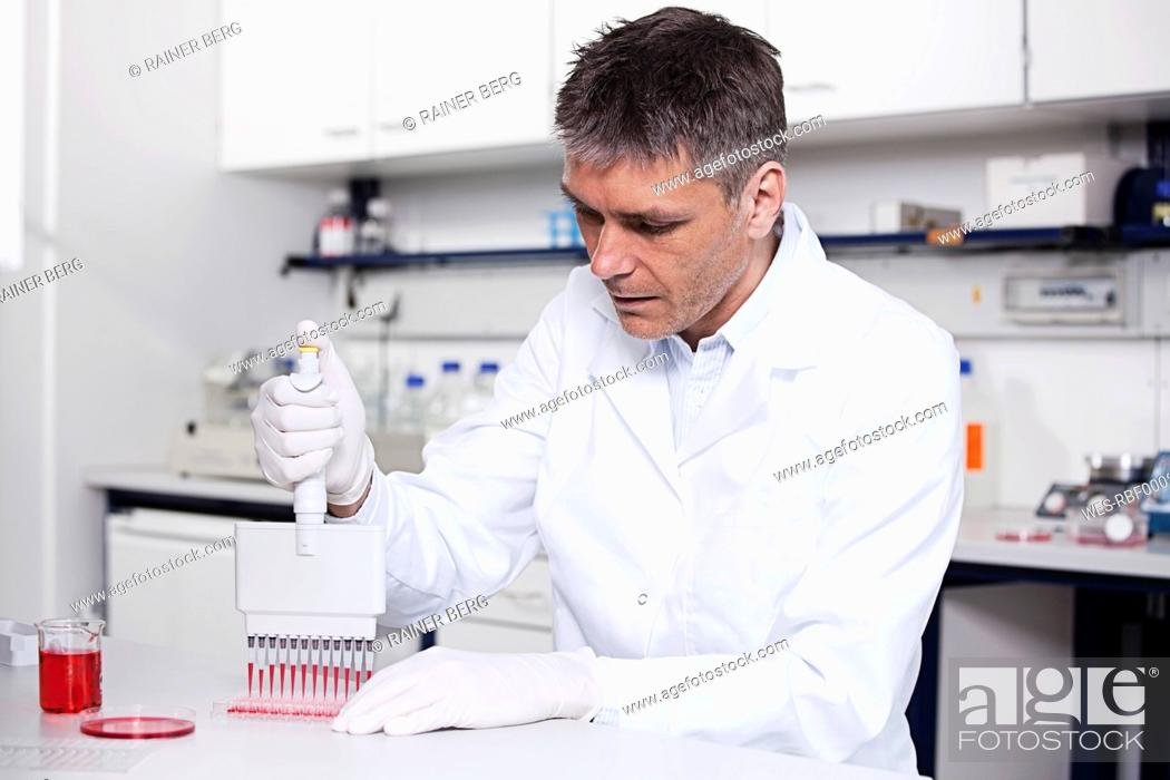 Stock Photo: Germany, Bavaria, Munich, Scientist pouring red liquid with pipette in test tray for medical research in laboratory.