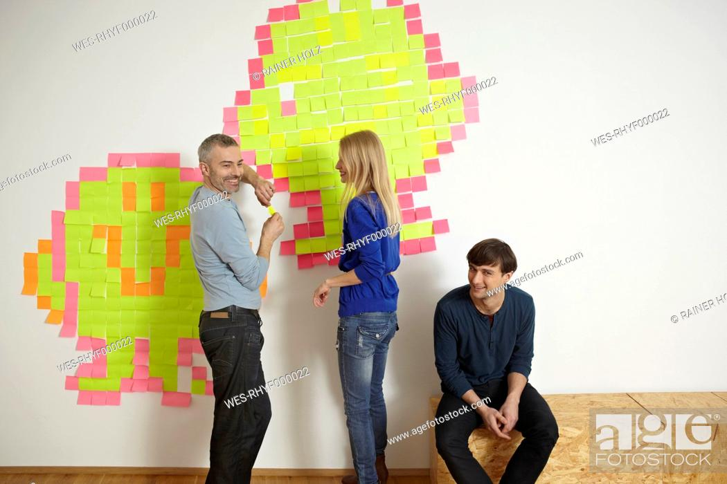 Stock Photo: Germany, Cologne, Men and woman with paper note on wall.